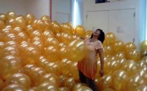 Holly and a bunch of golden balloons.